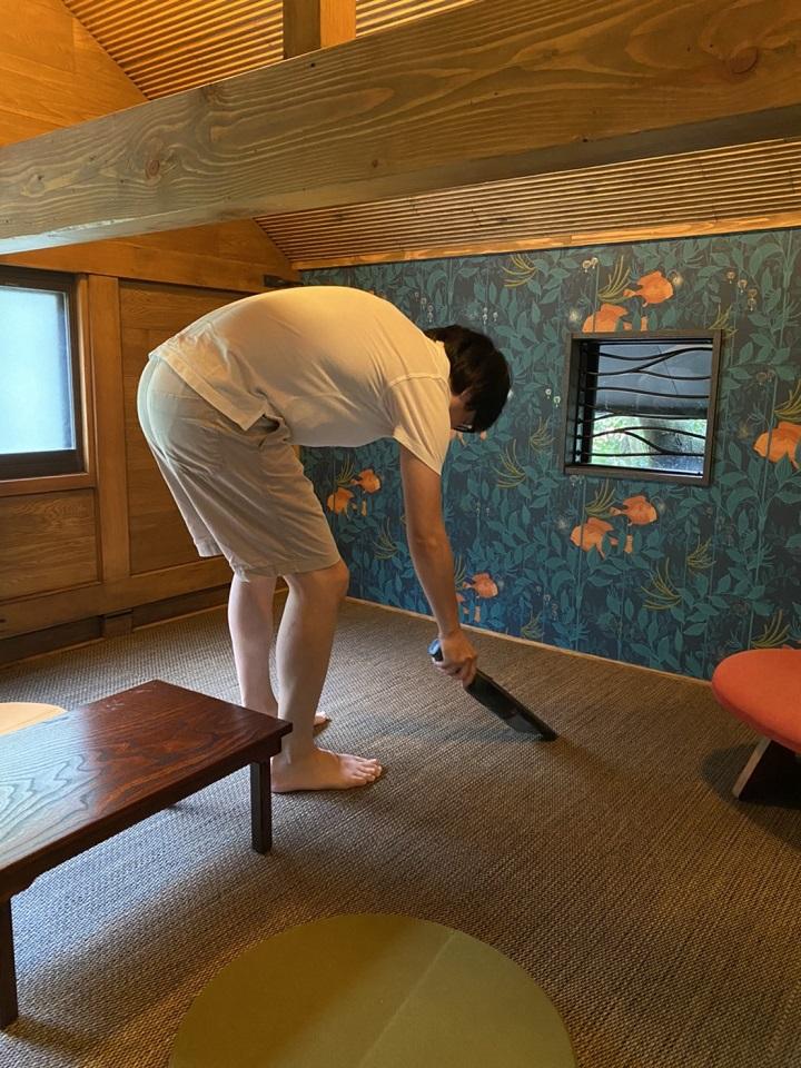 前かがみで二階の床を掃除