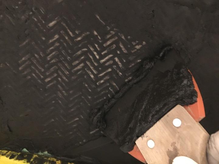 ゴムベラで余分な目地材を削り取る