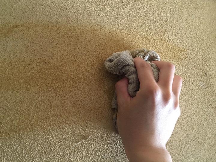 砂壁の表面を雑巾でふく